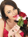 Sexy Young Woman Wearing Red Lingerie and Holding Red Roses Royalty Free Stock Photos