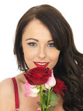 Sexy Young Woman Wearing Red Lingerie and Holding Red Roses Royalty Free Stock Images