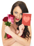 Sexy Young Woman Wearing Red Lingerie and Holding Red Roses Royalty Free Stock Photo