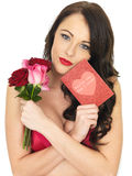 Sexy Young Woman Wearing Red Lingerie and Holding Red Roses Royalty Free Stock Photography