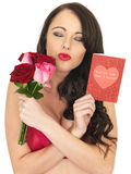 Sexy Young Woman Wearing Red Lingerie and Holding Red Roses Stock Photo