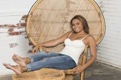 Young woman in white tank and blue jeans relaxes. Beautiful and young biracial woman wearing a white tank top and blue jeans sits in a large wicker chair royalty free stock photos
