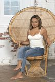 Young woman in white tank and blue jeans relaxes. Beautiful and young biracial woman wearing a white tank top and blue jeans sits in a large wicker chair royalty free stock photography