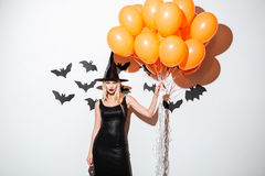 Sexy young woman in witch halloween costume holding orange balloons Royalty Free Stock Photos