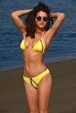 Sexy young woman in yellow bikini and sunglasses posing on the beach Stock Photography