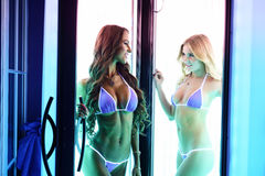 Sexy young women posing in tanning booth Stock Photo