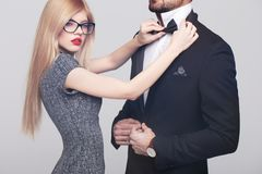 Young woman with red lips tying bow tie for stylish rich man royalty free stock photo