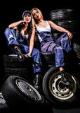Sexy young women sitting on a tires Royalty Free Stock Photography
