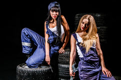 Sexy young women sitting on a tires Royalty Free Stock Image
