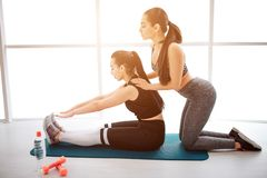 Young woman stand on knees behind asian model who keep legs straight. She help her to stretch. Models sit on. Young women stand on knees behind asian model who royalty free stock image