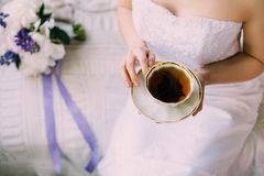Sexy zarte Braut im Nachtkleid oder im Hochzeitskleid mit decollete, eine Schale schwarzen Tee des Morgens in der Porzellanschale lizenzfreies stockfoto