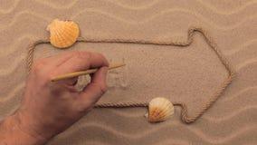 Seychellen-Aufschrift eigenhändig geschrieben auf den Sand, in den Zeiger gemacht vom Seil stock footage