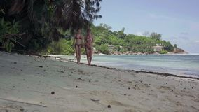 seychellen Praslineiland Twee slanke leuke meisjes die in badpakken op het strand van verbazend ontzagwekkend eiland lopen met stock footage