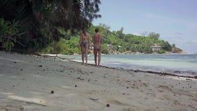 seychellen Praslineiland Twee slanke meisjes die in badpakken op het strand van verbazend ontzagwekkend eiland met palmen lopen stock footage