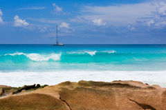 Seychelles beach with granite rock, turquoise water with sailing ship Stock Image