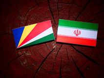 Seychelles flag with Iranian flag on a tree stump isolated. Seychelles flag with Iranian flag on a tree stump Stock Photography