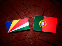 Seychelles flag with Portuguese flag on a tree stump isolated royalty free stock image