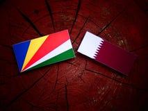 Seychelles flag with Qatari flag on a tree stump isolated Stock Photo