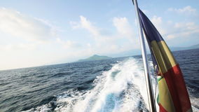 Seychelles flag waving on the boat. With perfect ocean and island view at the background in the middle of the day. Shot with Sony a7s stock footage