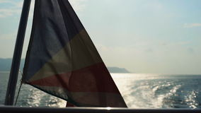 Seychelles flag waving on the boat. With perfect ocean and island view at the background at the sunset. Shot with Sony a7s stock footage