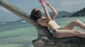 Seychelles Isla de Praslin La mujer joven atractiva que lee el libro que miente en el tronco de árbol grueso en el agua encendido almacen de metraje de vídeo