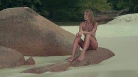 Seychelles Isla de Praslin Mujer bronceada hermosa en traje de baño con el cuerpo delgado que se sienta en la piedra grande en el almacen de video
