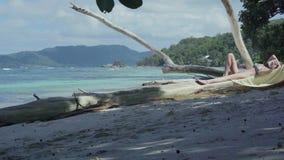 Seychelles Isla de Praslin Mujer delgada linda que lee el libro que miente en el tronco de árbol grueso en el agua en la playa almacen de metraje de vídeo