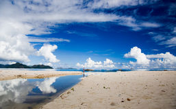 Seychelles island beach, blue sky, clouds, reflecting water surface, woman Stock Photos