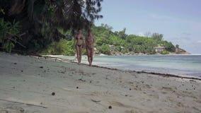 seychelles ?le de Praslin Deux filles mignonnes minces dans des maillots de bain marchant sur la plage de stupéfier l'île impress banque de vidéos