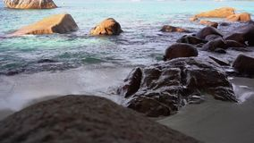 Seychelles Praslin wyspa Fale staczają się na piaskowatej plaży z kamieniami Tropikalny wyspa luksusu wakacje Turystyka, relaksuj zbiory wideo
