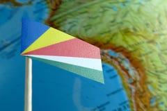Seychelles señalan por medio de una bandera con un mapa del globo como fondo Fotografía de archivo