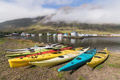 SEYDISFJORDUR, ICELAND - AUGUST 2018: waterfront view of old town timbered houses with plastic kayaks on foreground stock photos
