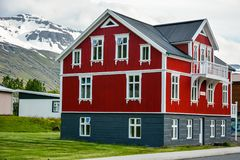 SEYDISFJORDUR, ISLANDIA, EL 24 DE JUNIO DE 2013: Casa roja colorida en Islandia del este en día de verano cubierto imagen de archivo libre de regalías