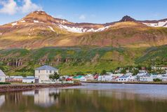 Seydisfjordur townscape Eastern Iceland Scandinavia. Seydisfjordur townscape with houses and surrounding landscape reflecting in Fjardara lake. Seydisfjordur is royalty free stock photos