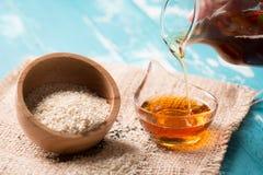 Sezamowi ziarna i sezamowy olej na starym drewnianym stole Fotografia Stock