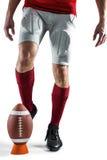 Sezione bassa del giocatore di sport che dà dei calci alla palla Fotografia Stock