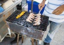 Sezione bassa del giovane che cucina i gamberetti sul barbecue, Koh Pha Ngan, Tailandia Fotografie Stock