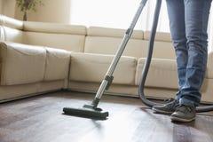 Sezione bassa del pavimento di legno duro di pulizia dell'uomo con l'aspirapolvere Immagine Stock