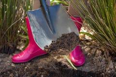 Sezione bassa del suolo di scavatura della donna con la pala in giardino Immagini Stock Libere da Diritti