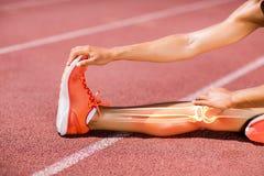 Sezione bassa dell'atleta femminile che allunga sulla pista Fotografie Stock Libere da Diritti
