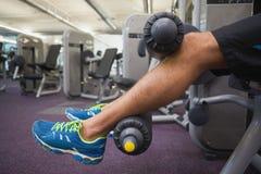 Sezione bassa dell'uomo che fa allenamento della gamba alla palestra Immagini Stock