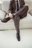 Sezione bassa dell'uomo d'affari che si siede sullo strato Fotografie Stock Libere da Diritti