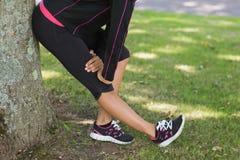 Sezione bassa della donna che allunga la sua gamba durante l'esercizio al parco Fotografia Stock Libera da Diritti