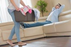 Sezione bassa della donna che cammina con il canestro di lavanderia mentre uomo che si rilassa sul sofà nel fondo Fotografia Stock Libera da Diritti