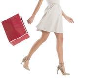 Sezione bassa della donna che cammina con il sacchetto della spesa Immagine Stock