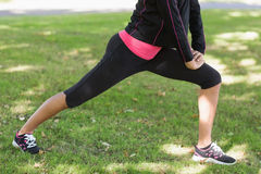 Sezione bassa della donna che fa che allunga esercizio in parco Fotografie Stock Libere da Diritti