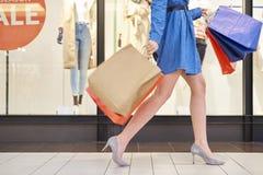 Sezione bassa della donna con i sacchetti della spesa che cammina nell'attività fotografia stock