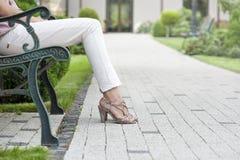 Sezione bassa della giovane donna che si siede sul banco di parco immagini stock