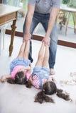 Sezione bassa delle ragazze di trascinamento del padre allegro sul pavimento di legno duro Immagine Stock