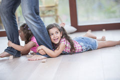 Sezione bassa delle ragazze di trascinamento del padre sul pavimento di legno duro Fotografia Stock Libera da Diritti